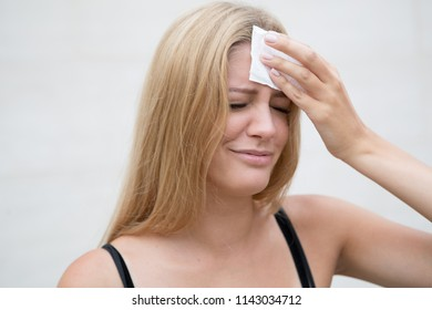Attractive woman drying her head with a tissue