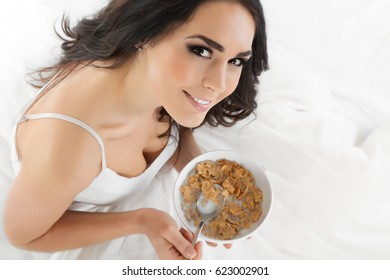Attractive woman eating cereals in bed