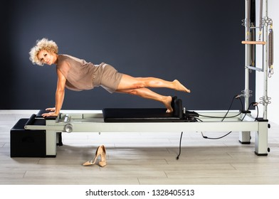 Attractive woman in elegant clothes doing push ups at gym