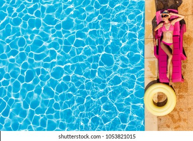 Attractive woman enjoying suntan by swimming pool