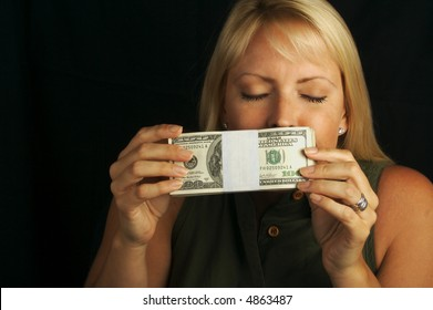 Attractive Woman Enjoys the Smell of Her Stack of Money on a Black Background
