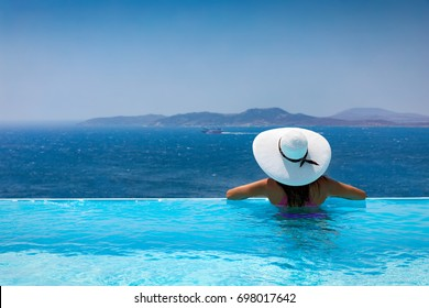 Attractive woman enjoys the view from the pool to the mediterranean sea