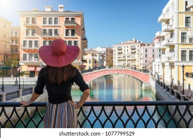Attractive woman enjoys the view to the Venice like Qanat Quartier on the Pearl in Doha, Qatar