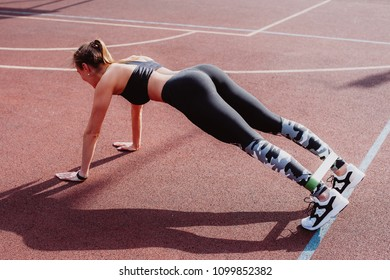 Attractive Woman Exercising With A Resistance Band On Floor outdoor