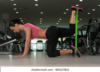 Attractive Woman Exercising With A Resistance Band On Floor In Gym As Part Of Fitness Training