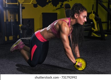 Attractive Woman Exercising With Wheel Roller For Abs On Floor In Gym As Part Of Fitness Training