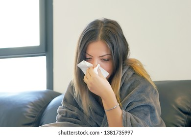 Attractive woman feeling cold, freezing, with napkin in a hand, wrapped in blanket, sitting on the sofa. Unhappy upset tired woman is sitting on a sofa at home suffering from a cold and using napkins.