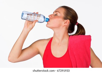 attractive woman in fitness clothes drinks from water bottle
