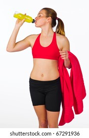 attractive woman in fitness clothes drinks from energy bottle