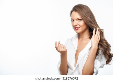 Attractive woman is flirting and smiling. She is inviting someone to come to her with gesturing with her hand. The lady is touching her hair. Isolated on background and copy space in left side