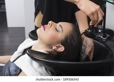Attractive woman getting hair washed in beauty salon