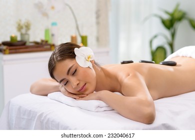 Attractive woman getting hot stone massage