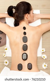 attractive woman getting hotstone massage on back