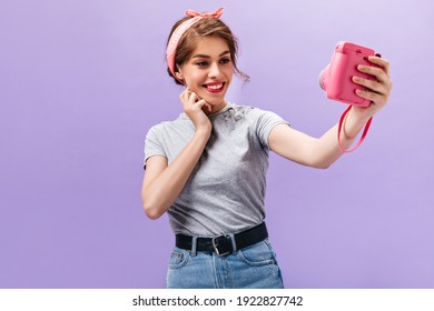 Attractive woman in grey shirt holds camera and takes selfie. Beautiful pretty girl with pink lips in stylish bandana and denim skirt smiling..