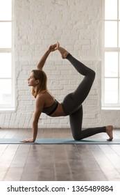 Attractive woman in grey sportswear, bra and leggings practicing yoga, doing tiger exercise, attractive girl standing in Bird dog pose, working out at home or in yoga studio, vertical photo