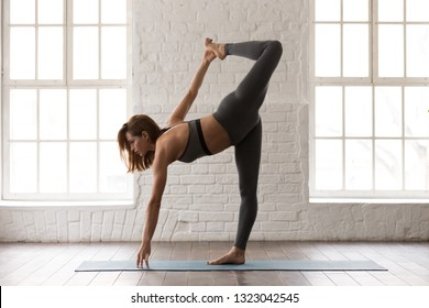 Attractive woman in grey sportswear, pants and bra practicing yoga, beautiful sporty girl standing in Half Moon pose, Ardha Chandrasana exercise, working out at home or in yoga studio