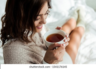 attractive woman in grey sweater holding cup of tea at morning