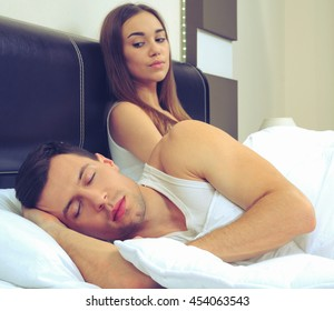 Attractive woman grieves while her husband is sleeping at home