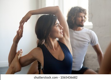 Attractive woman and a group of young sporty people practicing yoga lesson, doing Eka Pada Rajakapotasana exercise, Mermaid pose, working out, indoor close up, students training in club, studio