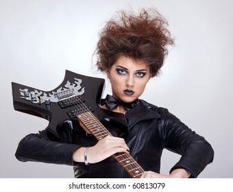 attractive woman guitarist holding her guitar on shoulder