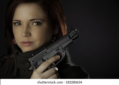 An attractive woman with a gun