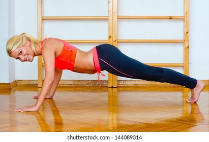 attractive woman in gym working on push ups
