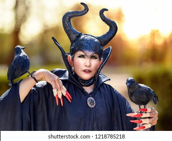 Attractive woman in a halloween costume as a wizard with fake birds and fake fingernails
