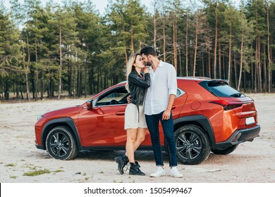 attractive woman and handsome man kissing and hugging near car