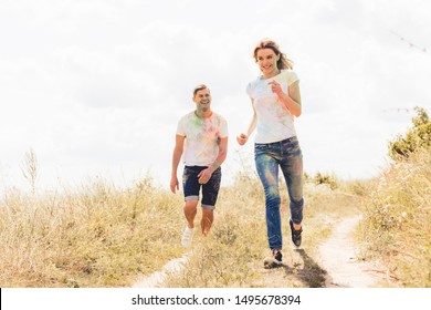 attractive woman and handsome man smiling and running outside