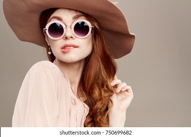 8121f1e429d3 attractive woman in a hat and glasses bites her lip on a light background  portrait