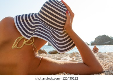 Attractive woman with hat on the beach