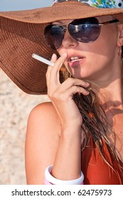 attractive woman in a hat smoking a cigarette