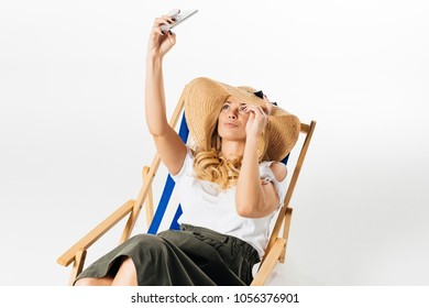 Attractive woman in hat taking selfie and resting in deck chair on white background