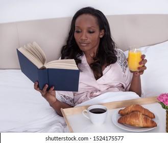 Attractive woman is having breakfast in bed