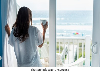Attractive woman having drink at the beach looking out the window