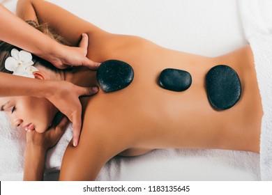 attractive woman having stone therapy at spa salon