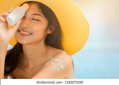 Attractive woman with healthy skin applying sunscreen on a sunny day and holding holding blank sunscreen UV protective lotion bottle packaging cosmetic template for your design.
