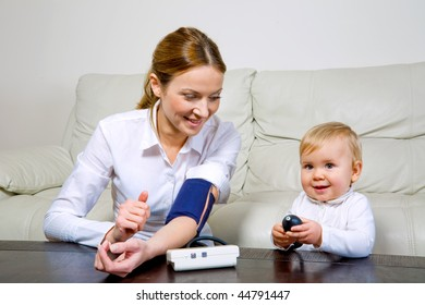 Attractive woman and her baby daughter with a blood pressure meter