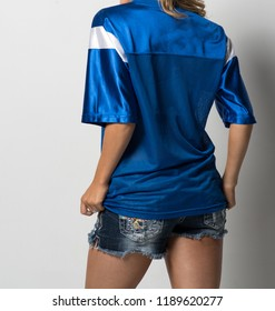 Attractive Woman with Her Back Turned, Wearing a Blue and White Football Jersey