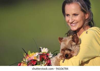 Attractive woman holding adorable Yorkshire Terrier