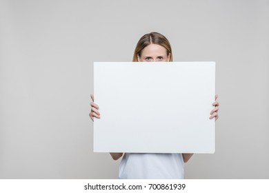 attractive woman holding empty blank board, isolated on grey