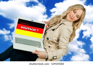 attractive woman holding laptop with german language sign on the screen