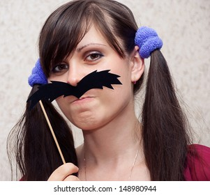 Attractive woman holding a mustache on a stick.