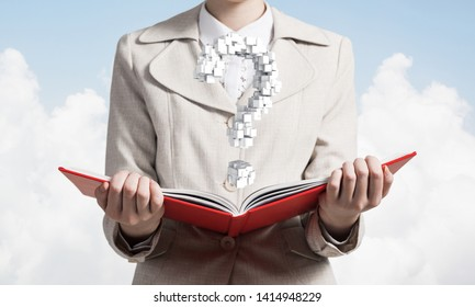 Attractive woman holding open notebook with question mark from cubes. Business consultation and legal assistance. Elegant woman in business suit with open book in hands on background of skyscape