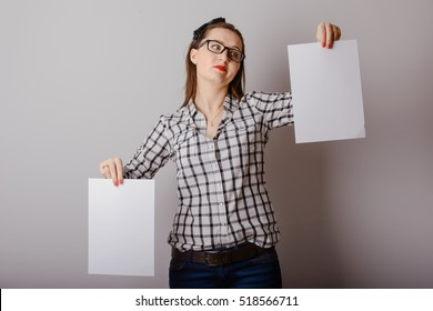 Attractive woman holding paper blank in her hands.