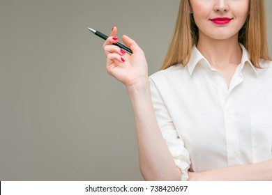 attractive woman holding a pen in hand, thinking, background, with copy space, for advertising