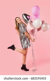 Attractive woman holding several differently shaped and coloured balloons posing in studio on pink background.