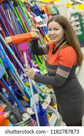 Attractive woman housewife buying new mop in hypermarket store for housekeeper, looking at camera
