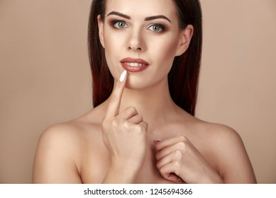 Attractive woman with ideal face touching her lips with finger beige or light brown background
