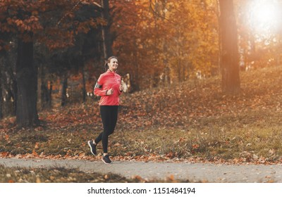 Attractive Woman Jogging. Autumn Outdoor. Female Runner in Park. Fitness and Wellness Concept. Healthy Lifestyle. Young Beautiful Woman. Sport Lifestyle. Listening Music Composition.